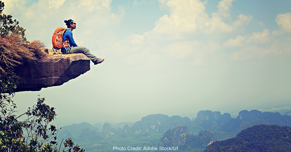 successful woman backpacker sit on mountain peak cliff