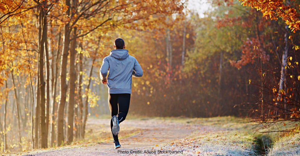 Young man running at park during autumn morning.