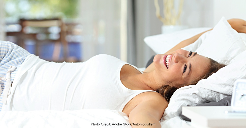 Girl waking up stretching arms on the bed