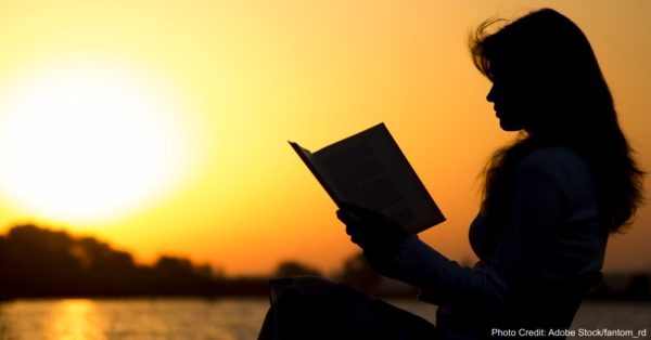 silhouette of a young beautiful woman at dawn sitting on a folding chair and carefully staring at the open book
