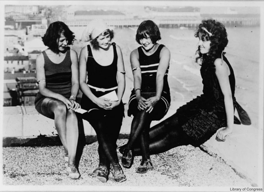 1920s women in swimsuits, still wearing stockings on public beach