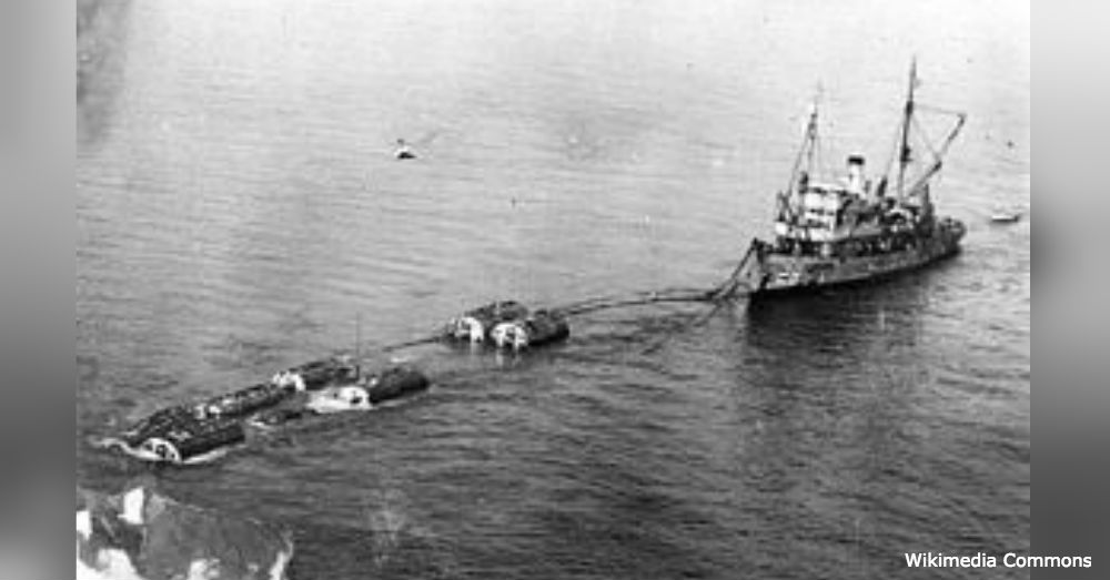 The damaged S-51 being transported below massive pontoons.