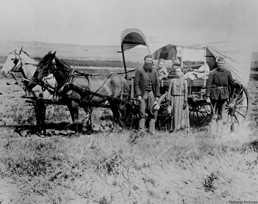 Settler family in front of their wagon.