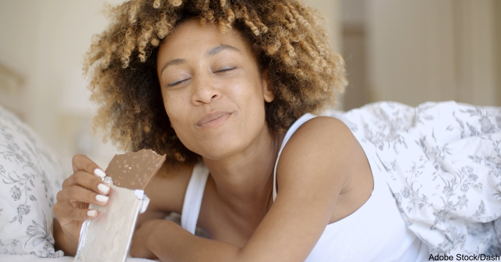 Woman Eating Chocolate In Bed At Home