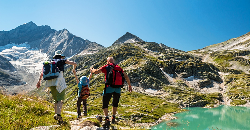 family with child hiking on holiday in austrian alps with lake and glacier view