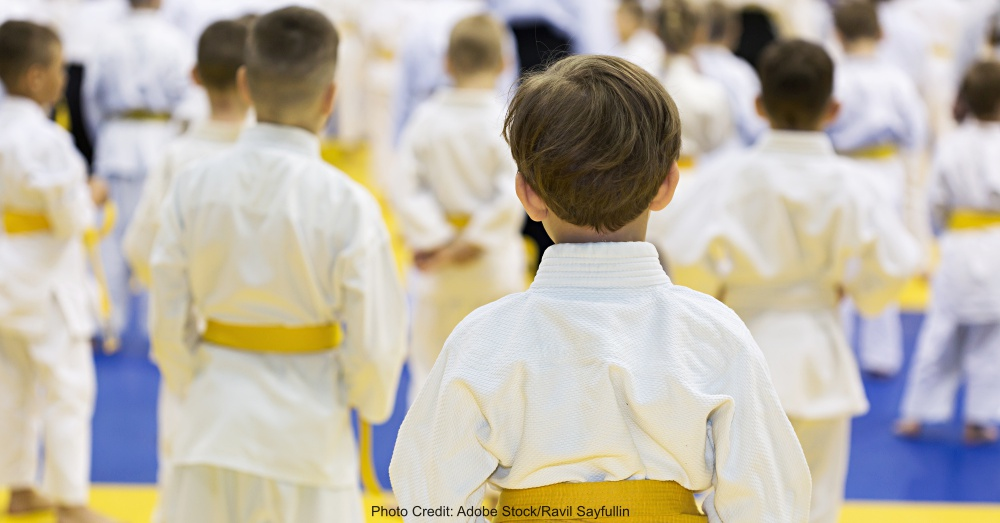 Children in kimono sitting on tatami on martial arts seminar