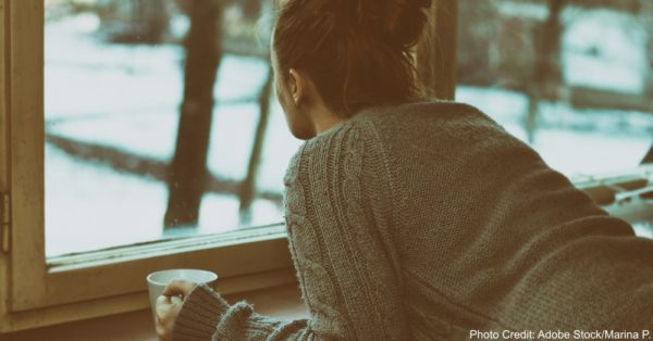 Sad woman by the window with y cup of coffee in a hand