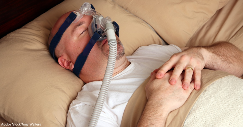 Man with sleep apnea using a CPAP machine in bed.