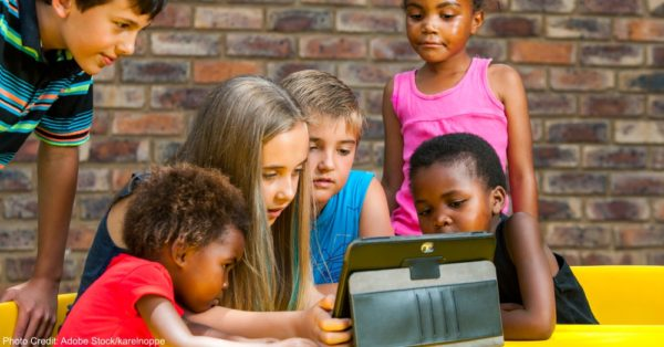 Diverse group of kids looking at tablet.