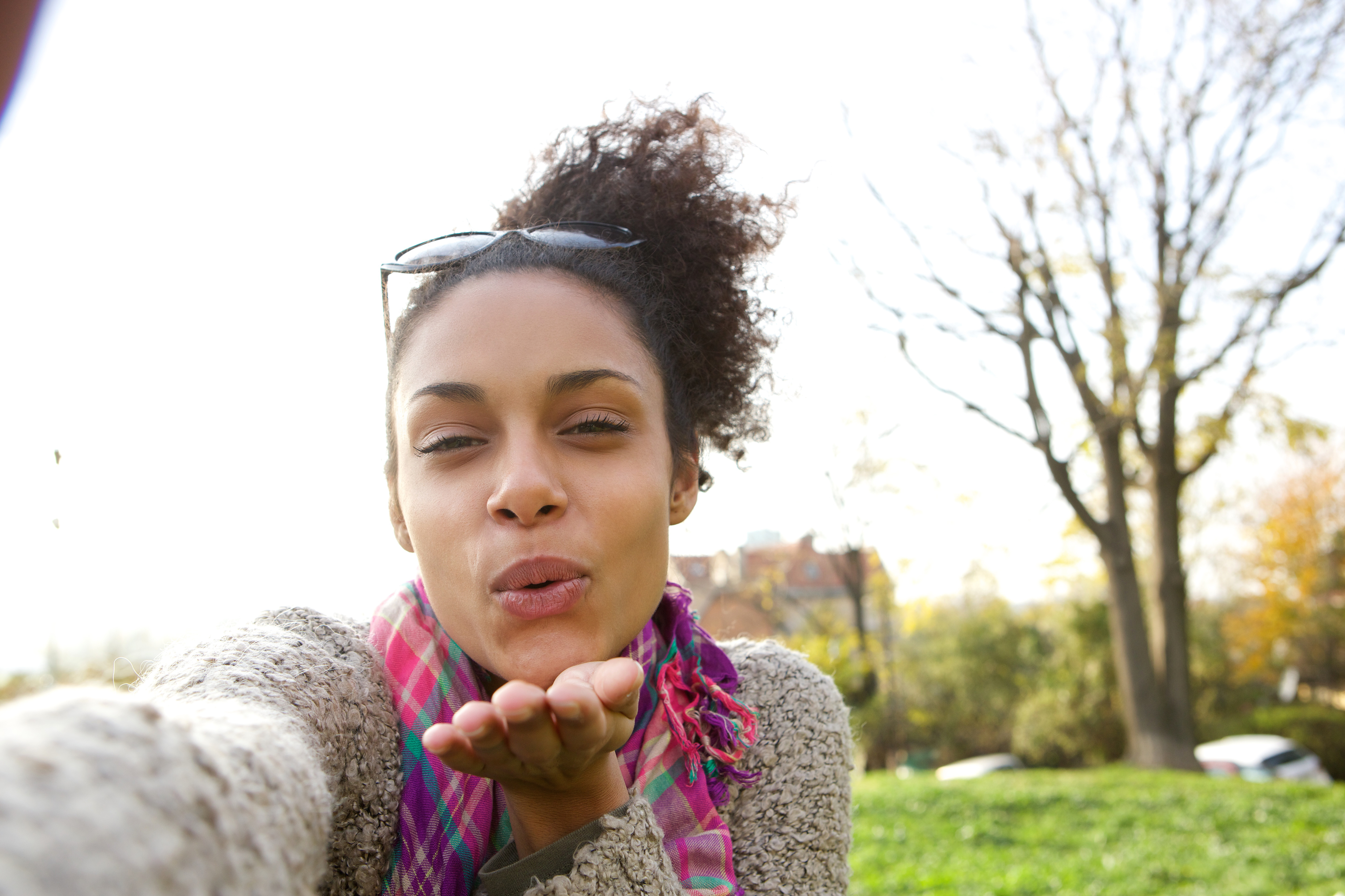 Selfie portrait of a young woman blowing a kiss