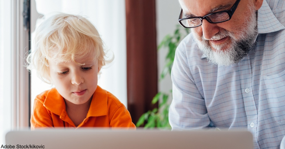 Grandfather and grandson using laptop