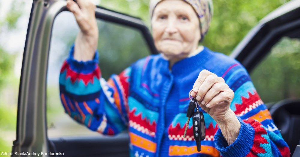 Senior woman holding car key and smiling, selective focus