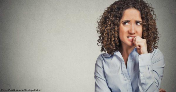 nervous looking woman biting her fingernails craving something