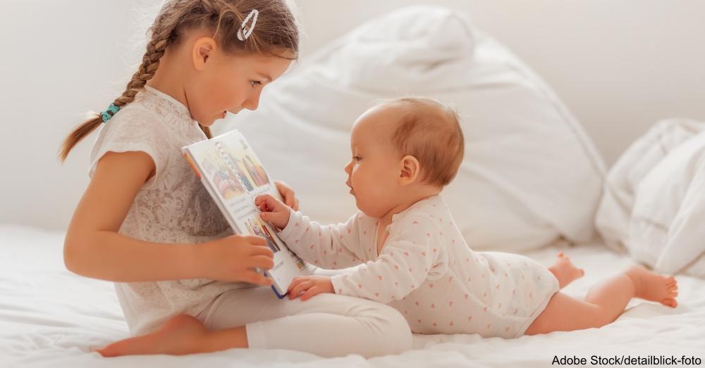 Mdchen liest ihrer kleinen Schwester etwas vor