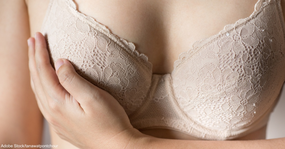 Woman touching breast.