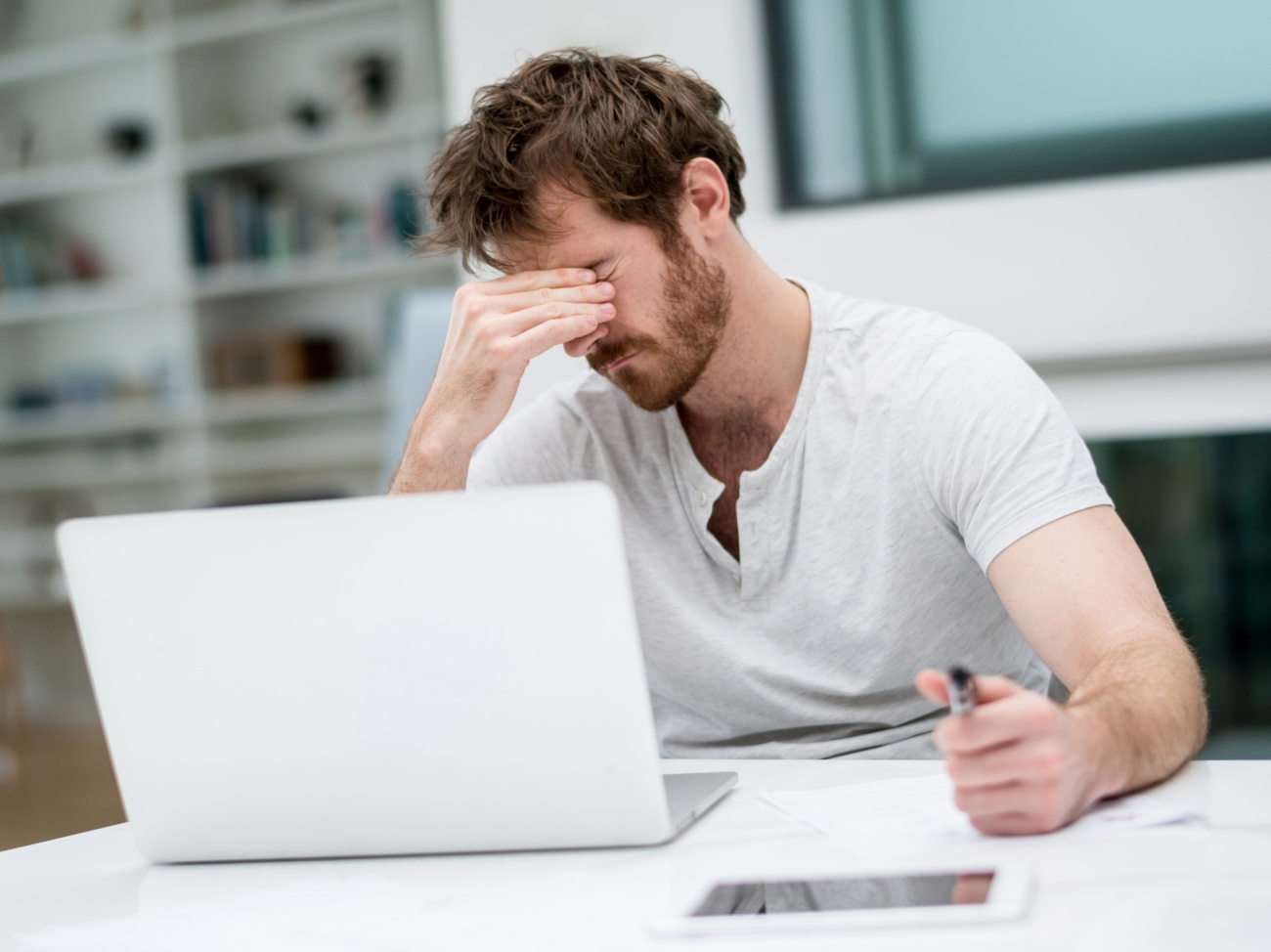 Tired man working online at home on a laptop computer - freelance designer