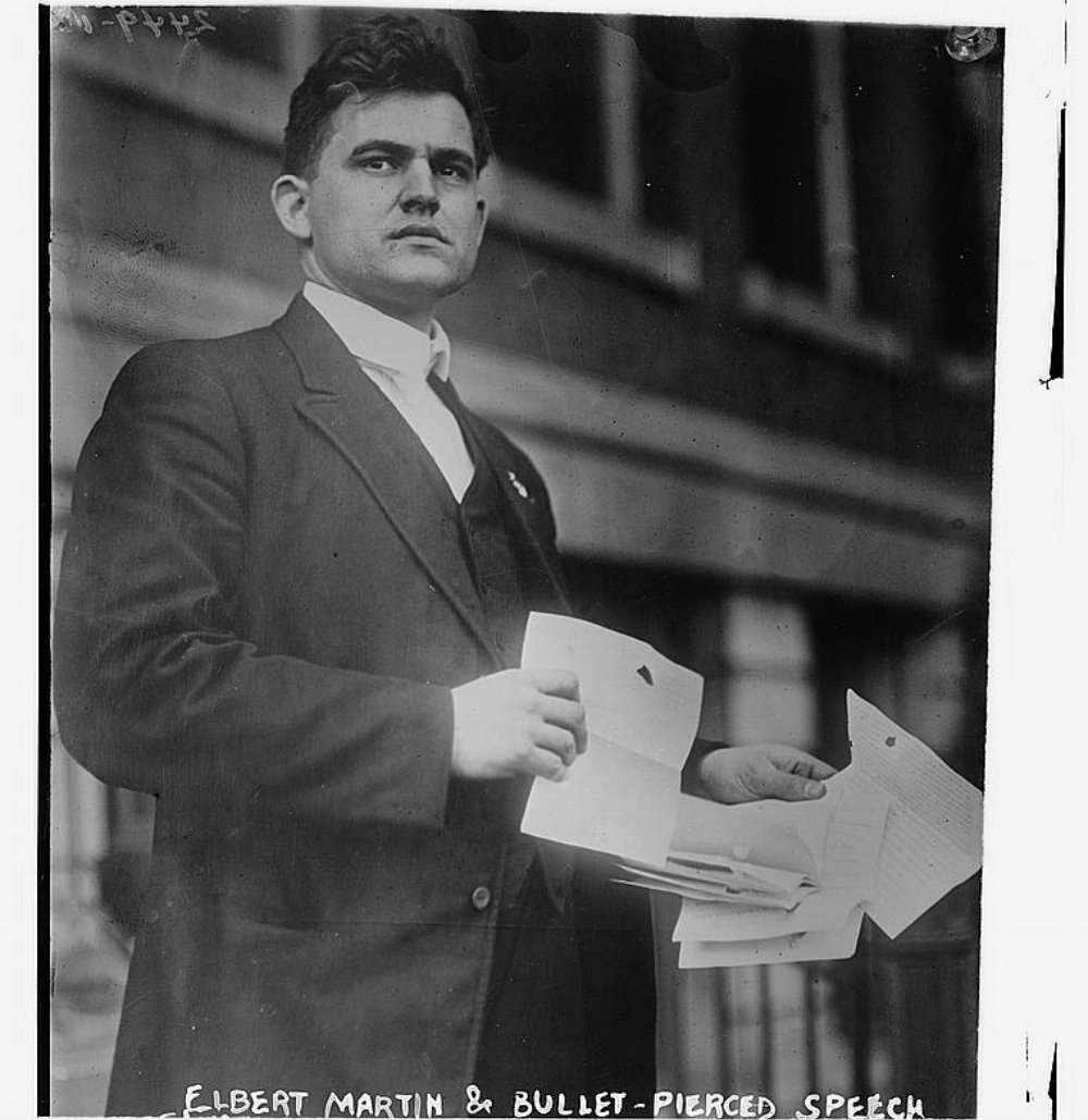 A photo of Roosevelt's secretary Elbert Martin holding the speech pierced by Schrank's bullet, via Flickr/ The Library of Congress