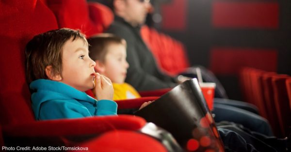 Father and two children, boys, watching cartoon movie in the cin