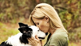 Girl kissing dogs head