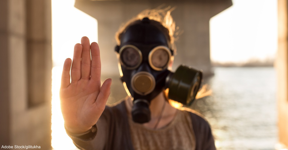 Ecological concept of air contamination. Woman in gas mask