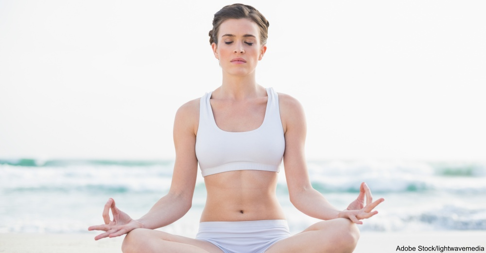 Peaceful slim brown haired model in white sportswear meditating in lotus position on the beach