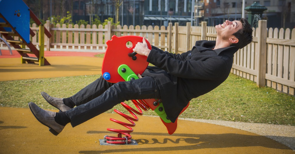 Young man reliving his childhood plying in a childrens playground riding on a colorful red spring seat with a happy smile in an urban park