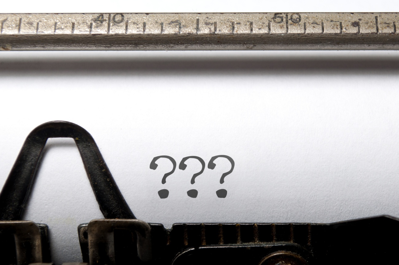 A type writer with question marks printed on the paper