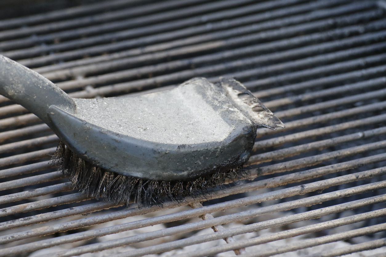 Grill with hot coals ready to bbq with the brush cleaning it.
