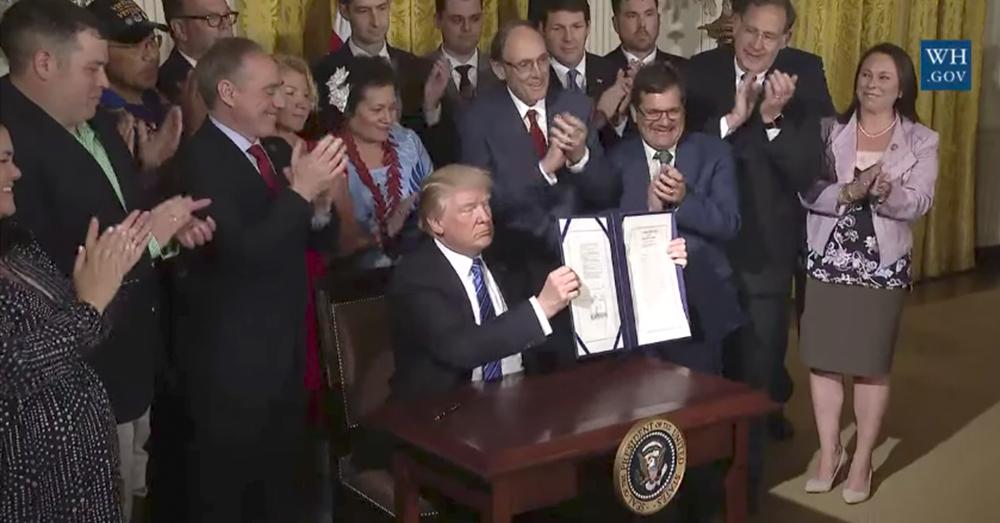 Photo: YouTube/The White House -- President Trump holds up the newly signed VA Accountability Act