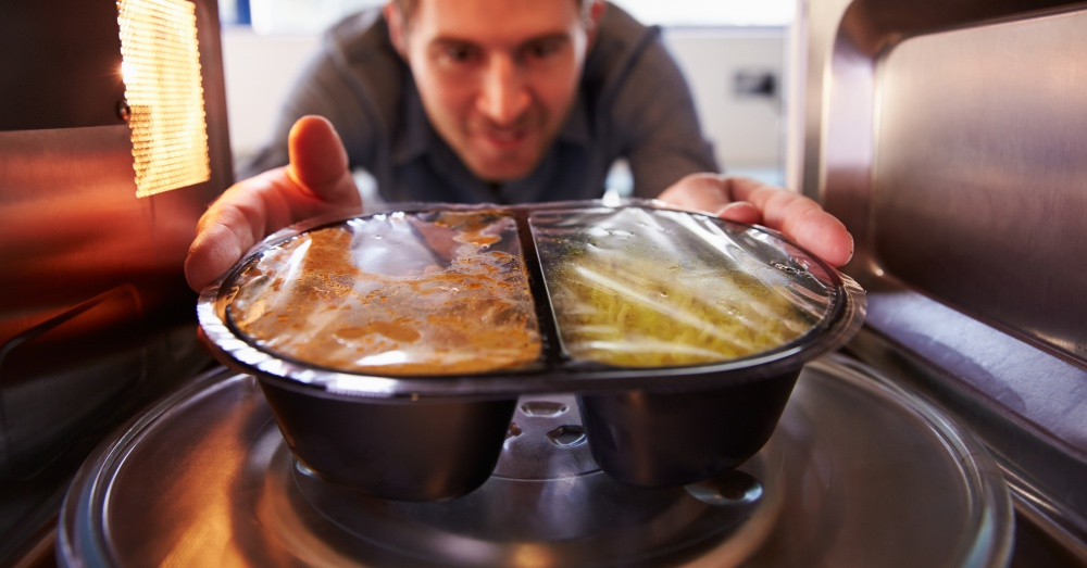 A man using a microwave to warm up a packaged meal
