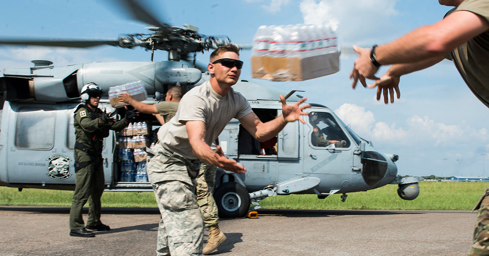Photo: U.S. Air Force/TSgt. Larry E. Reid Jr. -- Soldiers and Sailors load bottles of water onto a Navy helicopter for hurricane victims.