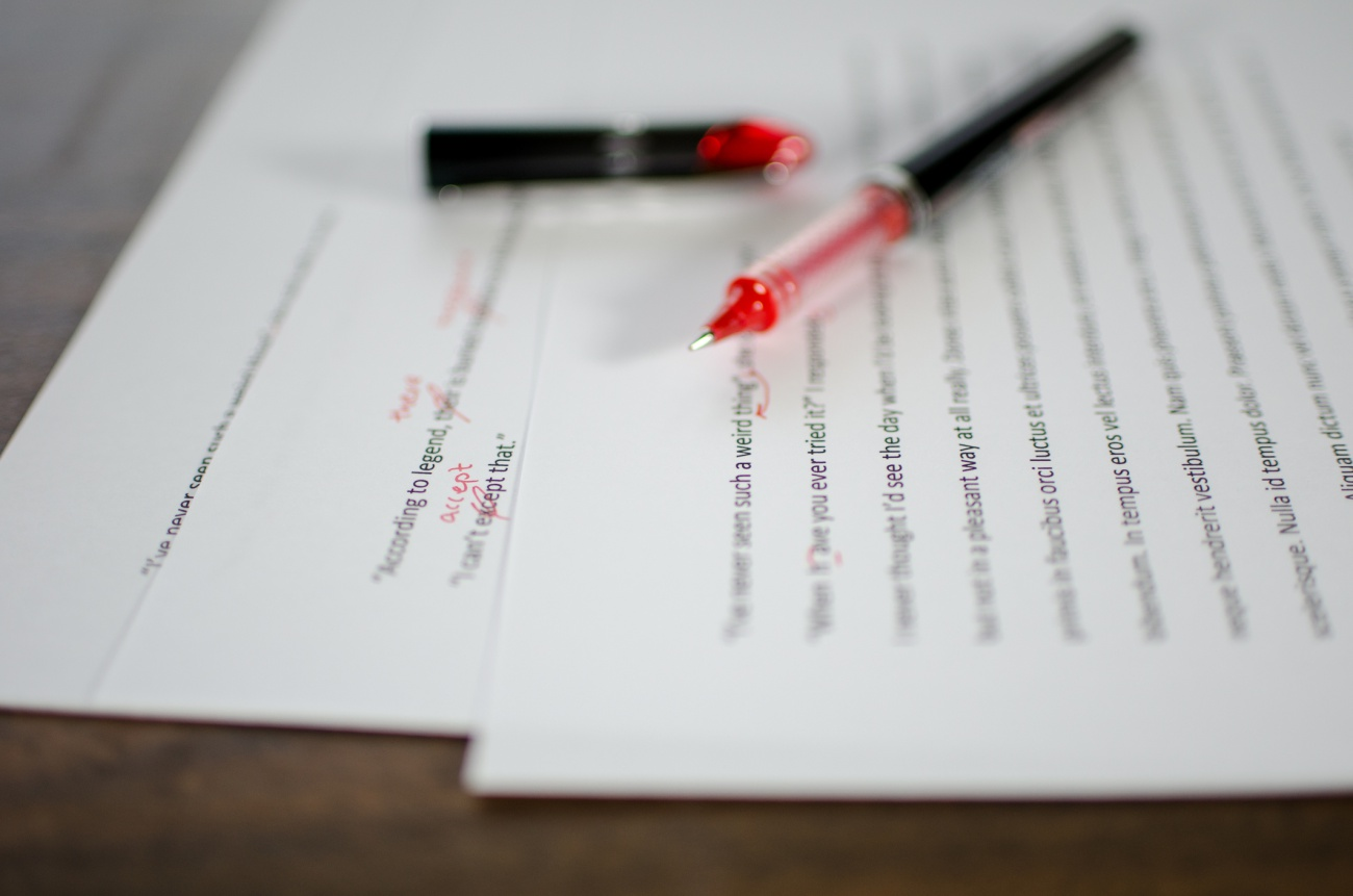 Red pen editing a manuscript