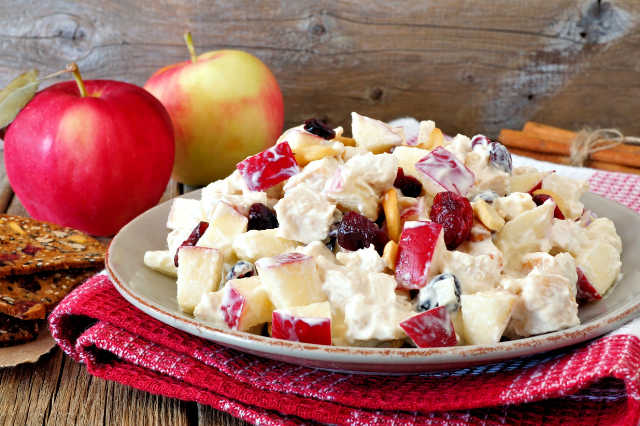 Autumn salad with chicken, apples, nuts, cranberries in yogurt dressing