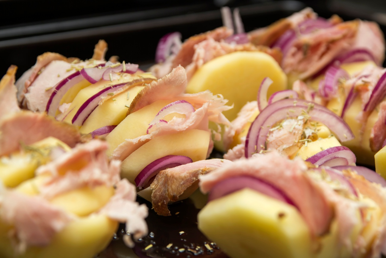 Potatoes stuffed with onion and pork ham in tray