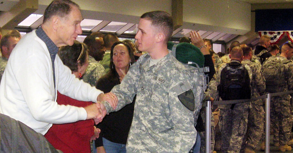 Pfc. Travis Kaufman, assigned to the 27th Brigade Support Battalion, 4th Brigade Combat Team, 1st Cavalry Division receives a hand shake from a USO volunteer as Kaufman departs the Dallas Fort Worth Airport while returning from Environment Moral Leave (EML) to continue the brigade's 15-month deployment in southern Iraq, Dec. 10. (U.S. Army photo by Sgt. 1st Class Damian Steptore)