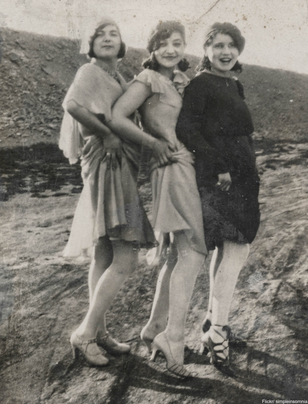 Three flappers hike their skirts