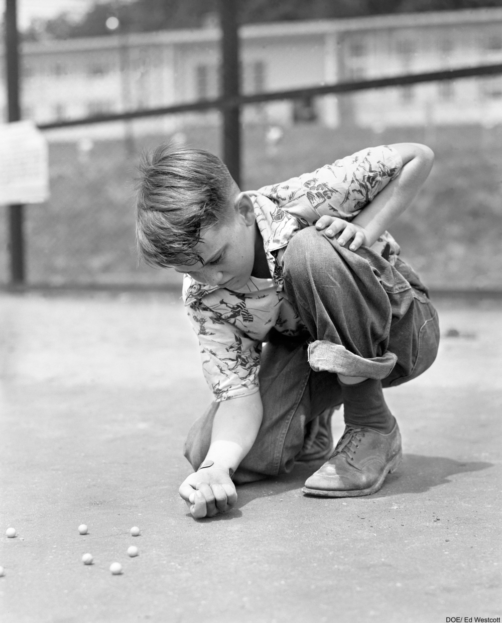 boy playing marbles on the ground