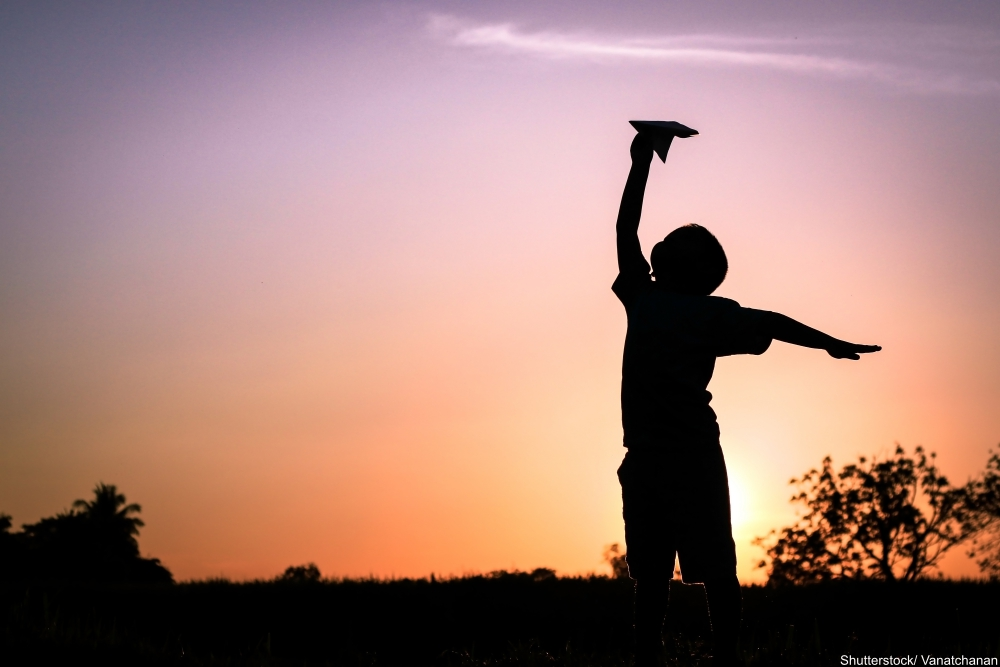 little boy playing with a paper airplane at sunset
