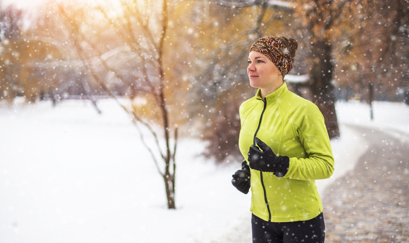 Young sport woman doing exercises during winter training outside in