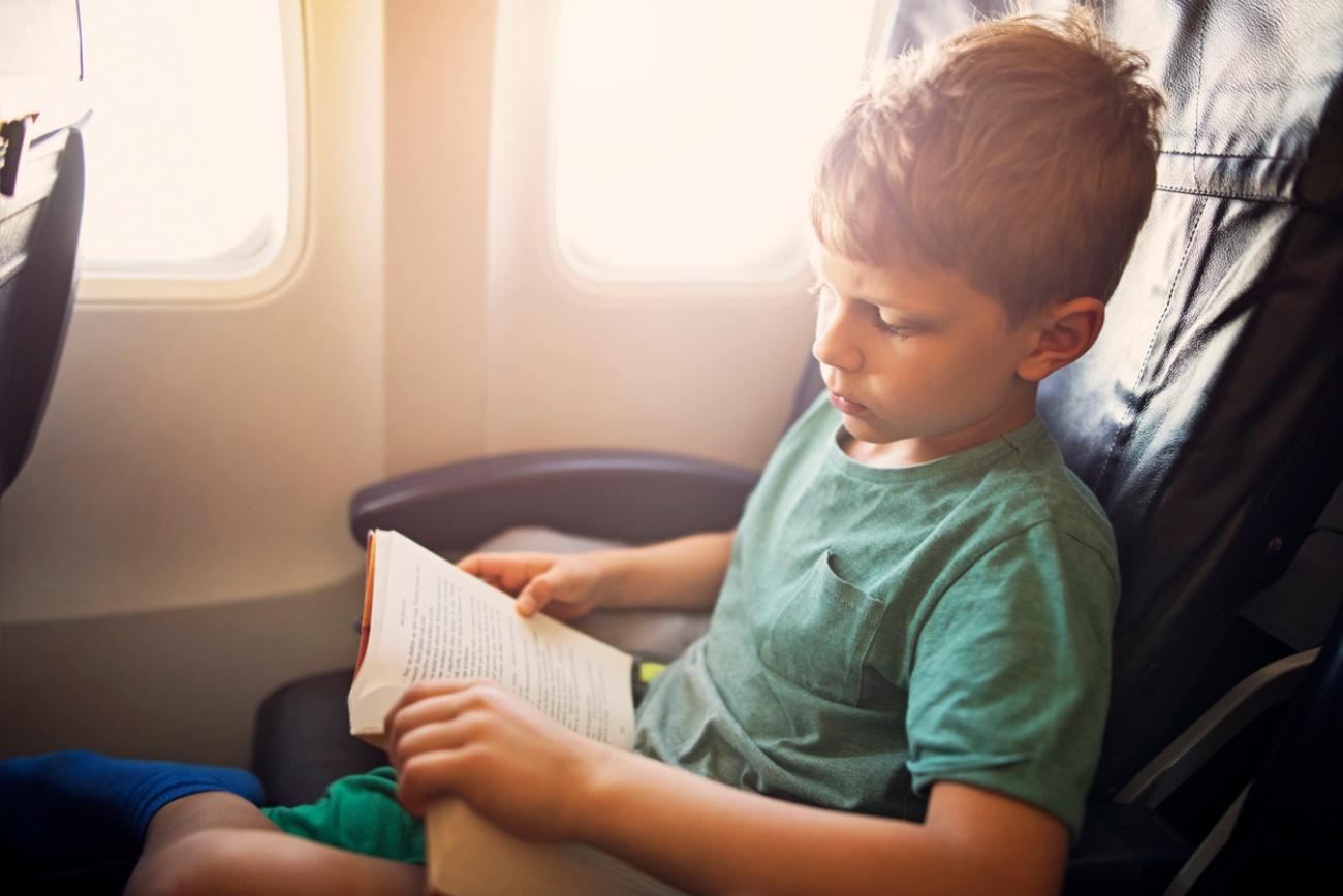 Little boy reading a book in plane