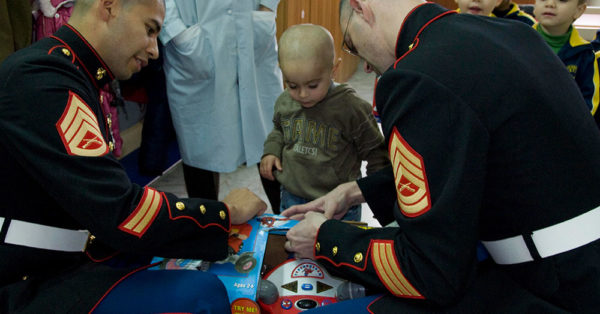 Source: Wikimedia Commons Staff Sgt. Denis Licona, left, assigned to Commander U.S. Naval Forces Europe-Africa/U.S. 6th Fleet, and Gunnery Sgt. Jarod Duke, assigned to Commander, Strike Force NATO staff, help open a gift for a boy during a community service event.