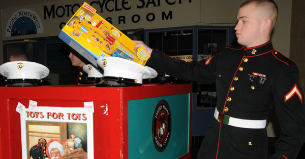 Source: Wikimedia Commons Pfc. Eric Tanis, assigned to Marine Corps Security Force Battalion (MCSFBn) puts toys in a collection box to support the Marine Toys for Tots foundation.