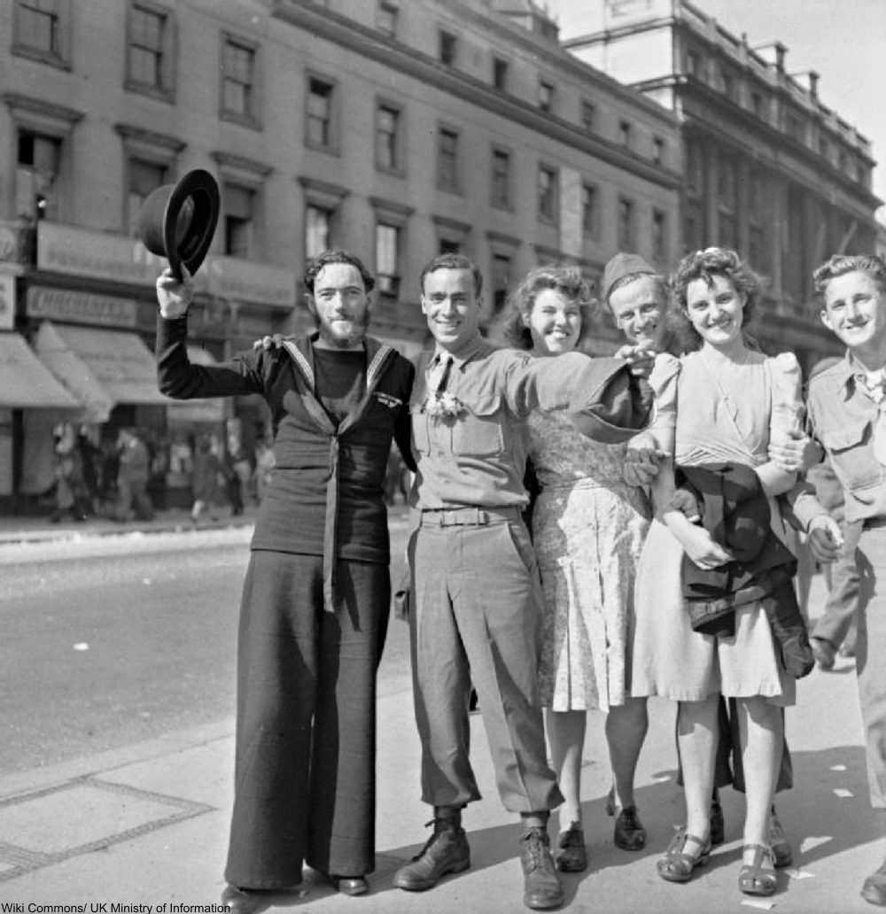 A New Zealand sailor raises his bowler hat in the sunshine as he celebrates Victory in Japan with several smiling American soldiers and English civilian women on the Strand in London. One of the GIs has a small spray of flowers pinned to his shirt.
