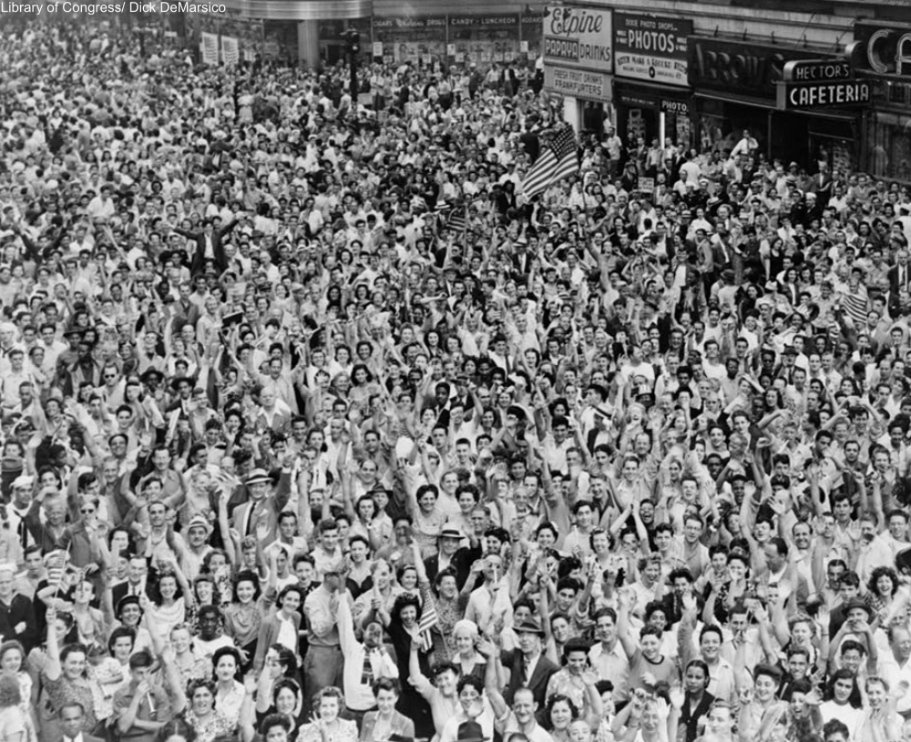 Crowd of people, many waving, in Times Square on V-J Day at time of announcement of the Japanese surrender in 1945