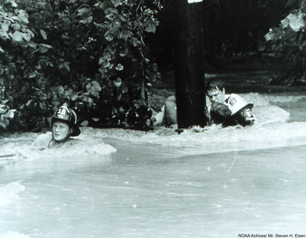 Dragging a rescued individual back to safety through the strong current The rescued man was lucky - many people have been killed by flash floods. Rockville, Maryland. July 15, 1975