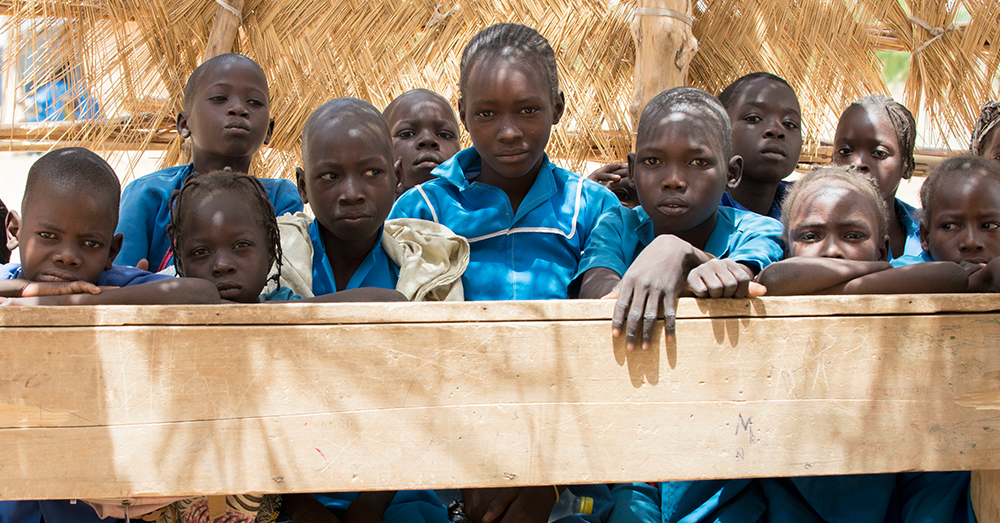 U.S. Army/Sean Kimmons -- Students share a desk while attending a school in northern Cameroon, while an Army civil affairs team visited to see how they could help improve security against Boko Haram militants.