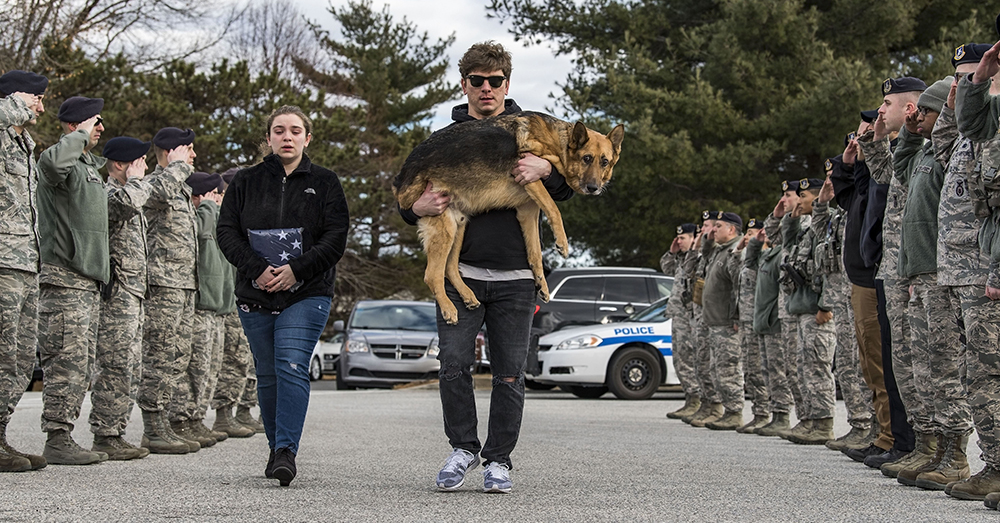 U.S. Air Force/Roland Balik -- Members of the 436th Security Forces Squadron render a final salute to retired Military Working Dog Rico as his former handler and current owner, retired Tech. Sgt. Jason Spangenberg, carries him to the Veterinary Treatment Facility on Dover Air Force Base.