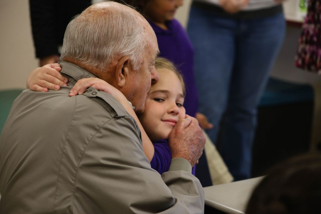A grandfather hugs and kisses his granddaughter in church.