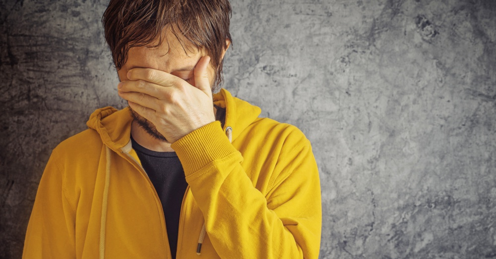 Adult Man with Chronic Migraine Headache Wearing Yellow Jacket.