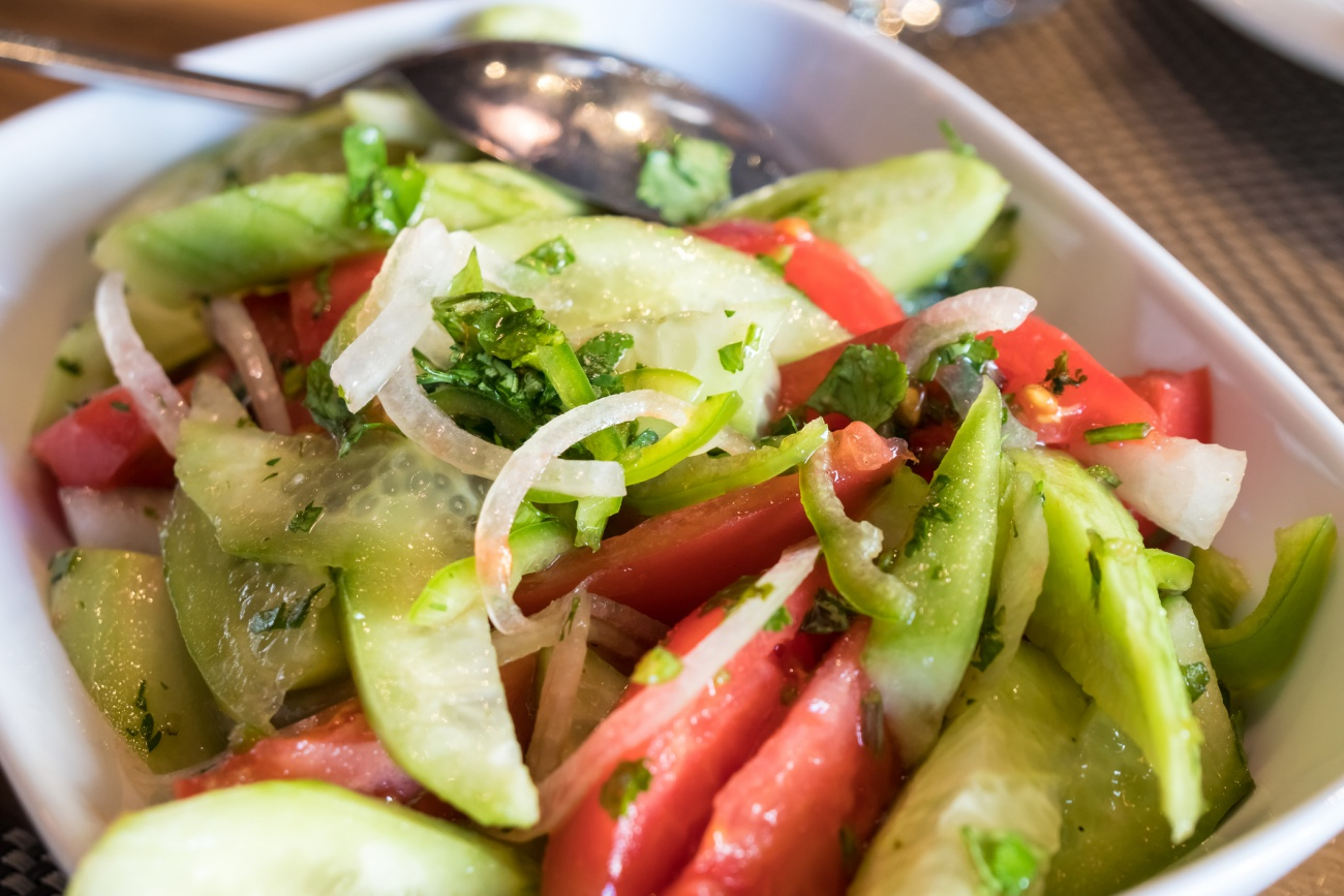 Tomato and cucumber salad with onion, pepper and parsly